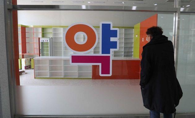 폐업한 화성 남양신도시 약국 앞에서 김완 기자가 내부를 살펴보고