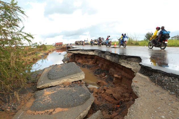 Motorcycles pass through a section of road damaged by Cyclone Idai in Nyamatanda about 50 kilometres...