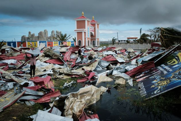 People collect metal sheets from a damaged supermarket to re-build their destroyed houses following the...