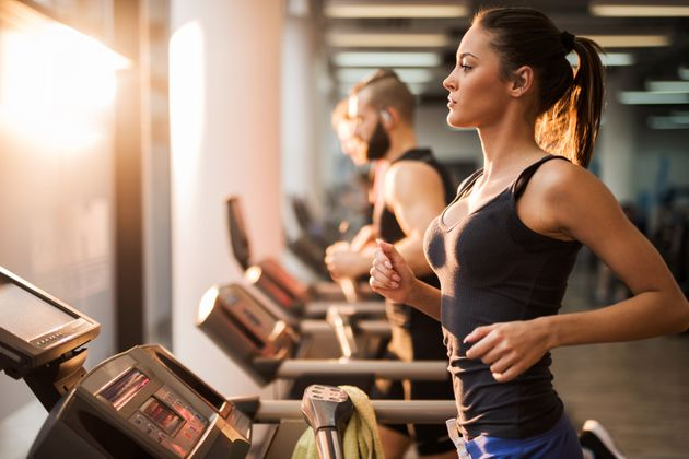 Young people exercising in a gym on treadmill. Focus is on