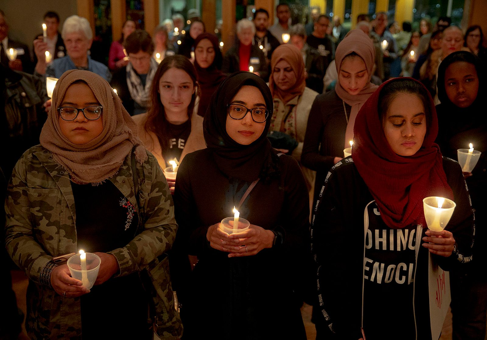 Syeda Sabeera, from left, Sumaiya Syed and Amina Choudhury stand with candles during a prayer service at St. James Episcopal Church on Saturday, March 16, 2019, in Austin, Texas. The service was held in honor of those killed and injured in Friday's mass shooting at two mosques in Christchurch, New Zealand. (Nick Wagner/Austin American-Statesman via AP)