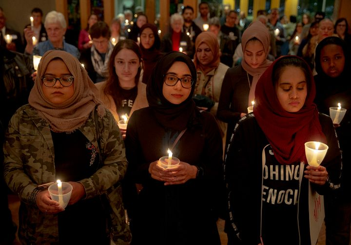 From left: Syeda Sabeera, Sumaiya Syed and Amina Choudhury stand with candles during a prayer service at St. James Episcopal