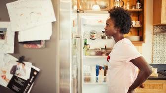 Hungry woman peering into refrigerator in kitchen
