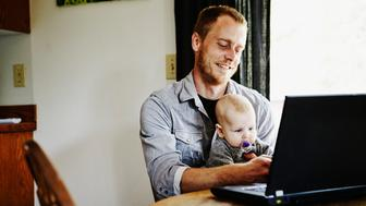 Smiling father sitting with baby on lap while working on laptop at dining table in home