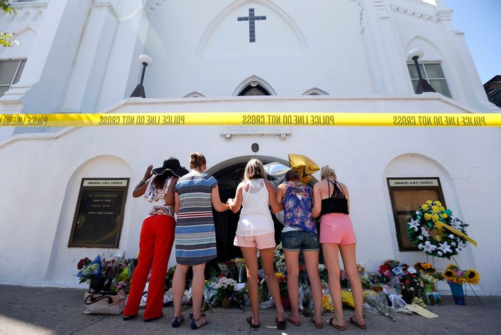 In this June 18, 2015, file photo, a group of women pray together at a makeshift memorial on the sidewalk in front of the Ema