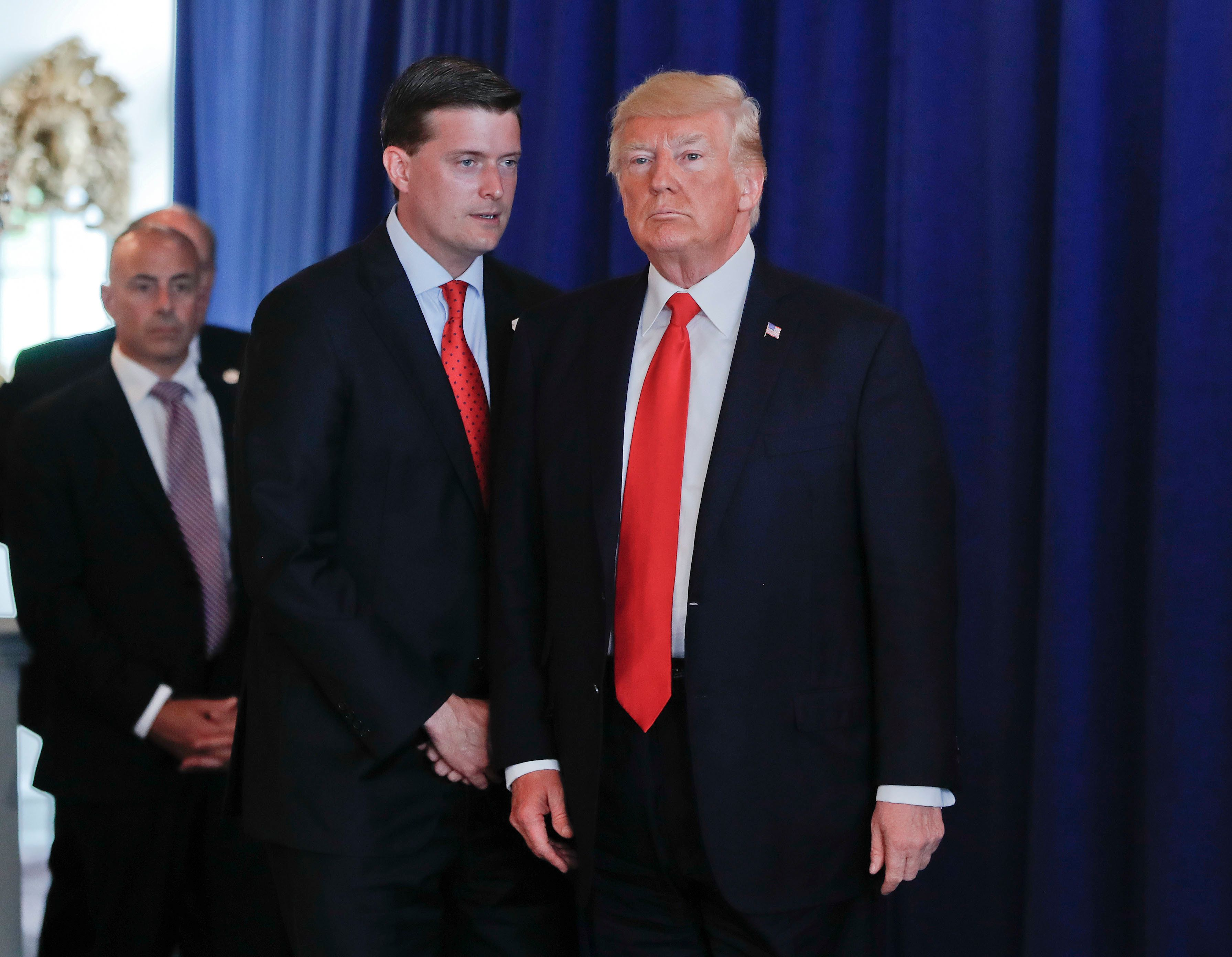 Rob Porter, left, White House Staff Secretary speaks to President Donald Trump after Trump made remarks regarding the on going situation in Charlottesville, Va., Saturday, Aug. 12, 2017 at Trump National Golf Club in Bedminister, N.J. Porter reminded Trump that he still needed to sign the Veteran's Affairs Choice and Quality Employment Act of 2017. (AP Photo/Pablo Martinez Monsivais)
