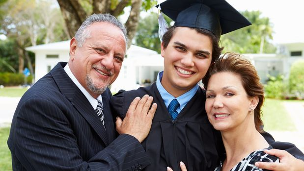 Hispanic Student And Parents Celebrate Graduation Smiling To Camera