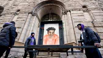 Farooq Al-Said, left, Jasiri X, center, and Jarrion Manning, right, hold a memorial display with a drawing of Antwon Rose II in front of the court house on the first day of the trial for Michael Rosfeld, a former police officer in East Pittsburgh, Pa., begins on Tuesday, March 19, 2019, in Pittsburgh. Rosfeld is charged with criminal homicide in the fatal shooting of Antwon Rose II as he fled during a traffic stop on June 19, 2018. (AP Photo/Keith Srakocic)