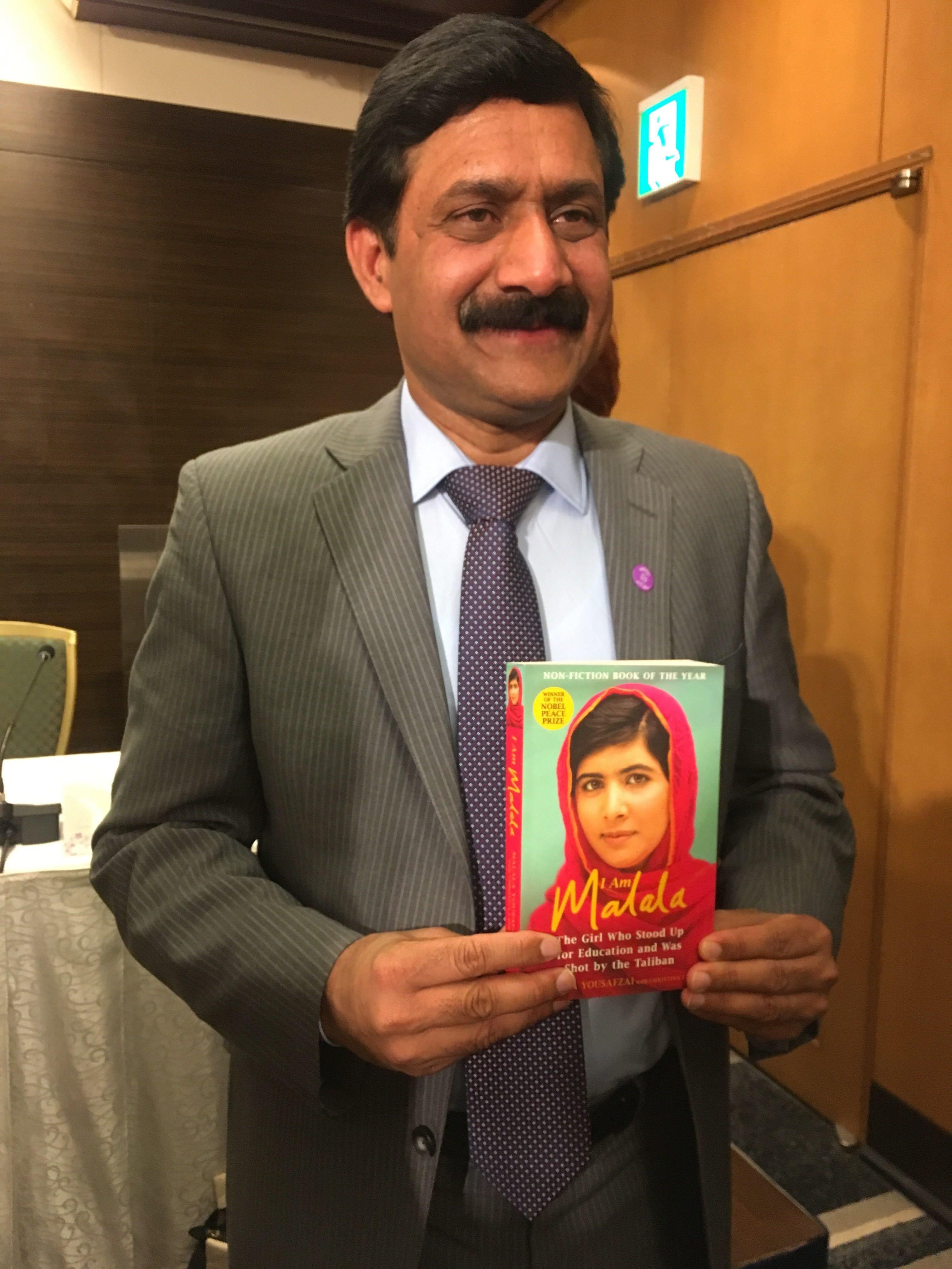 マララさんの著書を手に記念撮影に応じるジアウッディン・ユスフザイさん