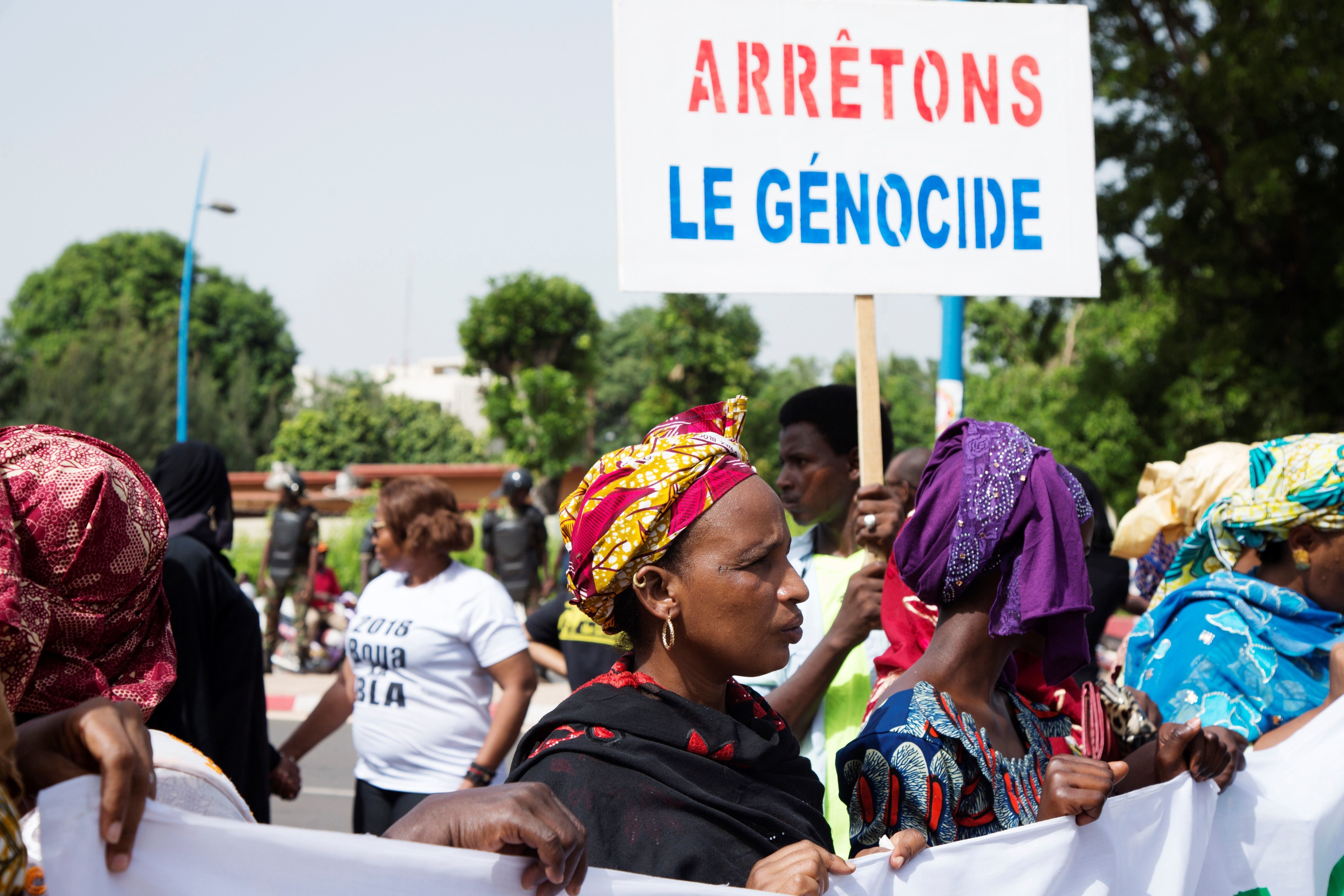 Malian women carry a banner 'Stop Genocide' as they take part in a march on June 30, 2018 in Bamako organised by the Mouvement Peul, an organisation of ethnic Fulani people, in response to a massacre in Koumaga, Mali. - On June 23, at least 32 civilians were killed and ten are missing following an attack in central Mali, believed to have been carried out by Muslim Fulani hunters. (Photo by ANNIE RISEMBERG / AFP)        (Photo credit should read ANNIE RISEMBERG/AFP/Getty Images)