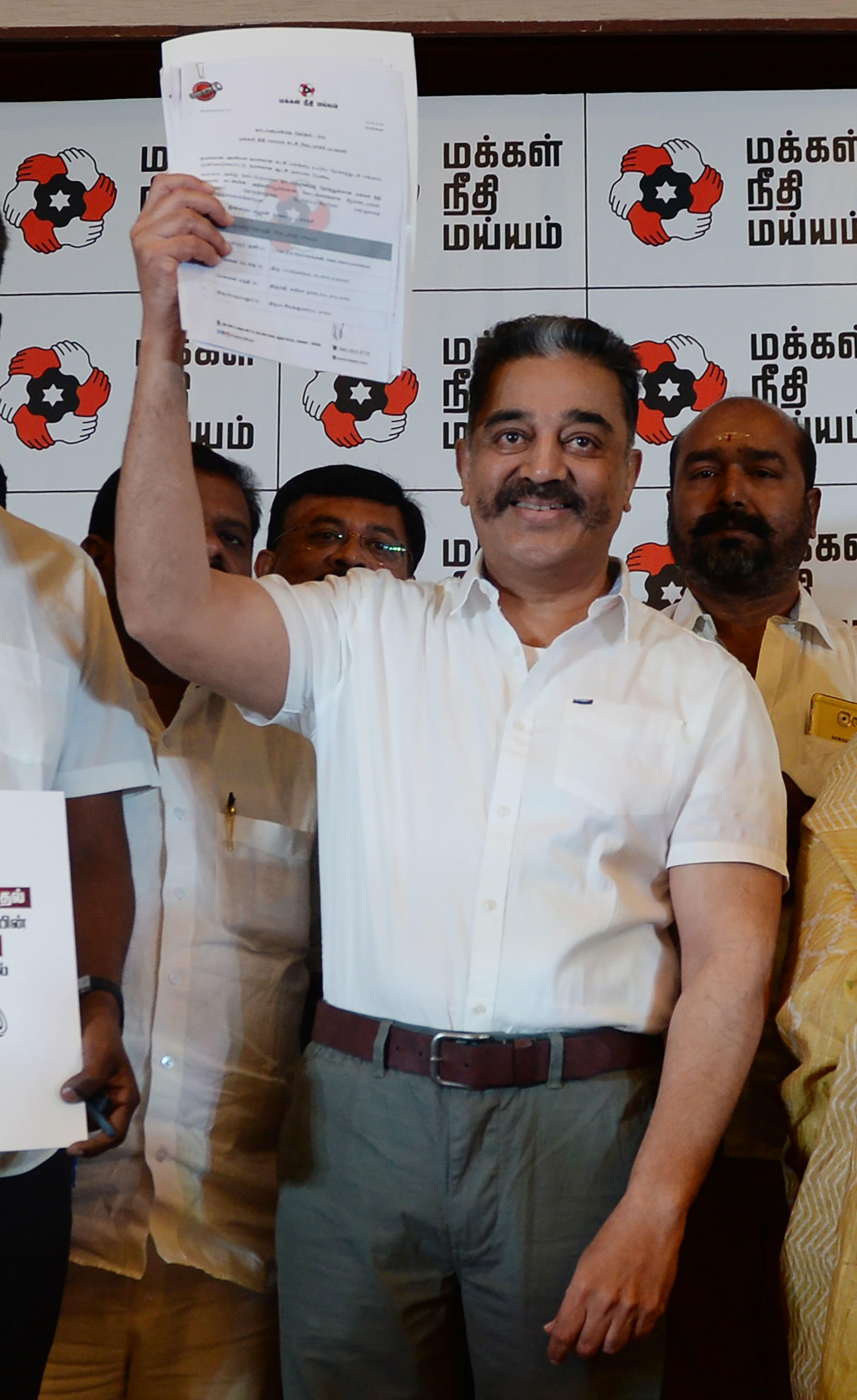Actor and founder of 'Makkal Needhi Mayyam' party Kamal Hassan displays a candidates list during the...