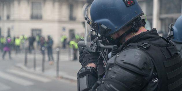 Un gendarme mobile tient un LBD40 face à des gilets jaunes, lors de l'Acte IV, le 8 décembre