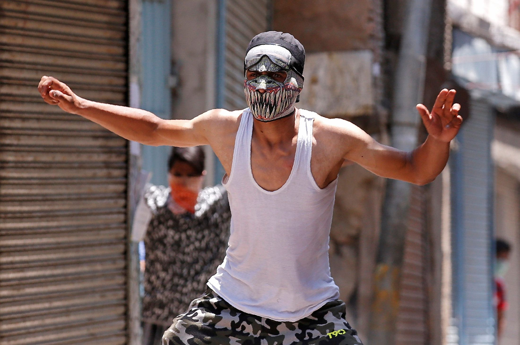 A masked protester reacts during a clash with police on the occasion of the death anniversary of Burhan