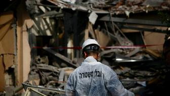 An Israeli police officer inspects the damage to a house hit by a rocket in Mishmeret, central Israel, Monday, March 25, 2019. An early morning rocket from the Gaza Strip struck a house in central Israel on Monday, wounding several people, including one moderately, an Israeli rescue service said, in an eruption of violence that could set off another round of violence shortly before the Israeli election. (AP Photo/Ariel Schalit)