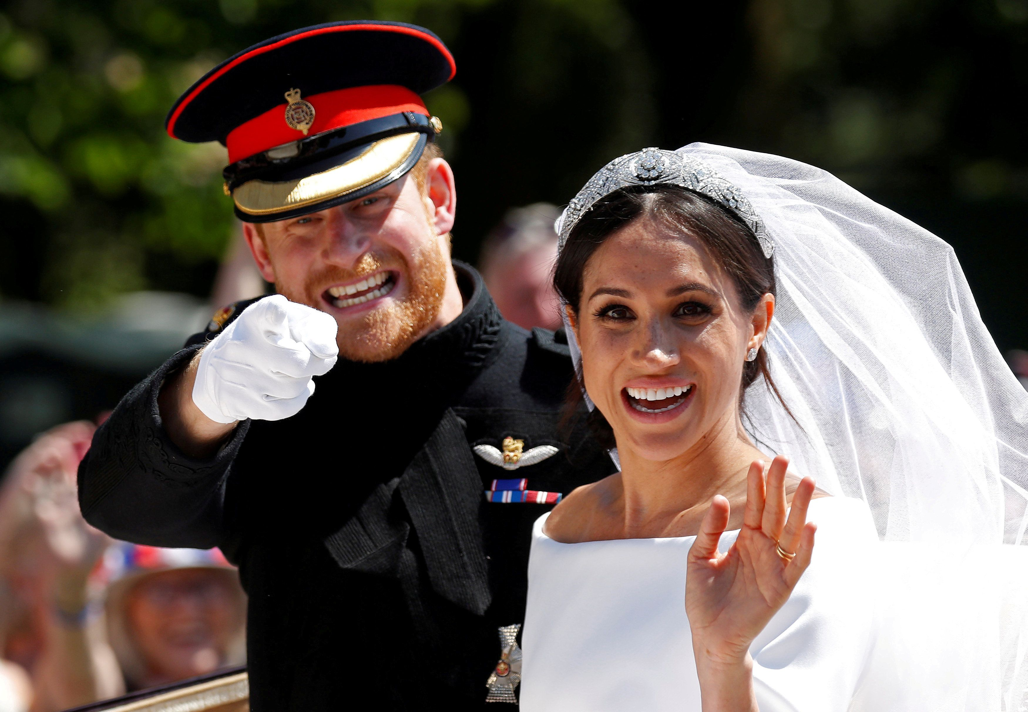 "Britain's Prince Harry gestures next to his wife Meghan as they ride a horse-drawn carriage after their wedding ceremony at St George's Chapel in Windsor Castle in Windsor, Britain, May 19, 2018. REUTERS/Damir Sagolj    SEARCH ""POY GLOBAL"" FOR FOR THIS STORY. SEARCH ""REUTERS POY"" FOR ALL BEST OF 2018 PACKAGES. TPX IMAGES OF THE DAY."