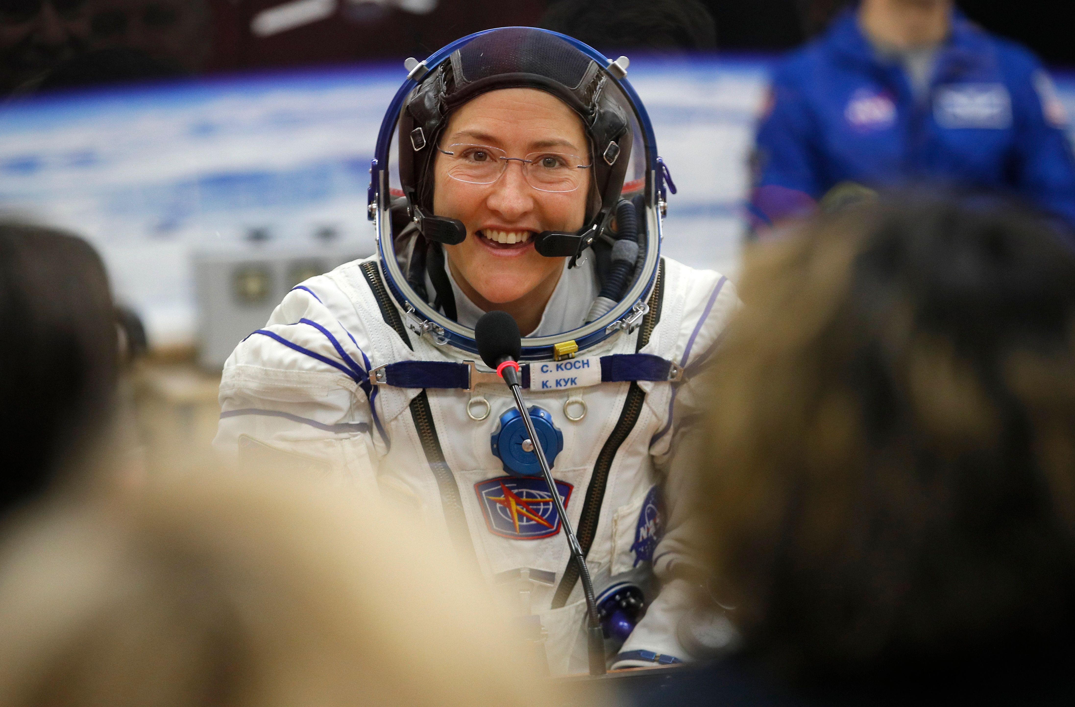 U.S. astronaut Christina Hammock Koch, member of the main crew of the expedition to the International Space Station (ISS), speaks with her relatives through a safety glass prior the launch of Soyuz MS-12 space ship at the Russian leased Baikonur cosmodrome, Kazakhstan, Thursday, March 14, 2019. (AP Photo/Dmitri Lovetsky, Pool)