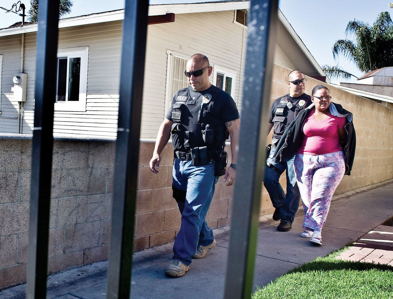 TOP PHOTO: Cheree Peoples outside of the apartment where she lives when her 17-year-old daughter, Shayla, is at Children's Hospital of Orange County. Peoples was arrested six years ago for Shayla's repeated truancy despite ample evidence given to the Orange County school showing Shayla suffers from sickle cell anemia, which leaves her in constant pain and requires frequent hospitalization. (Credit: Tara Pixley for HuffPost) <br>ABOVE: Buena Park police officers Luis Garcia (left) and James Woo escort Peoples, 33, to their patrol car on April 18, 2013. She was handcuffed and under arrest.