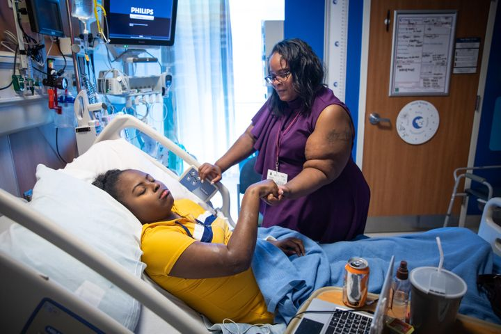 Peoples massages Shayla, who is being treated for sickle cell anemia at Children's Hospital of Orange County, on March 10.