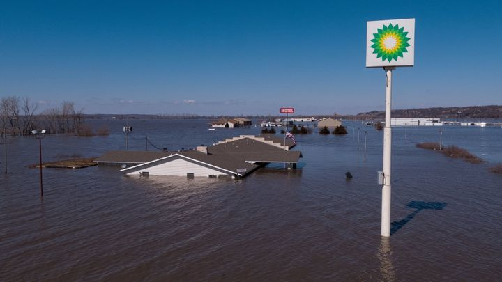 A gas station sign rises above the devastating floodwaters in a Midwest town.