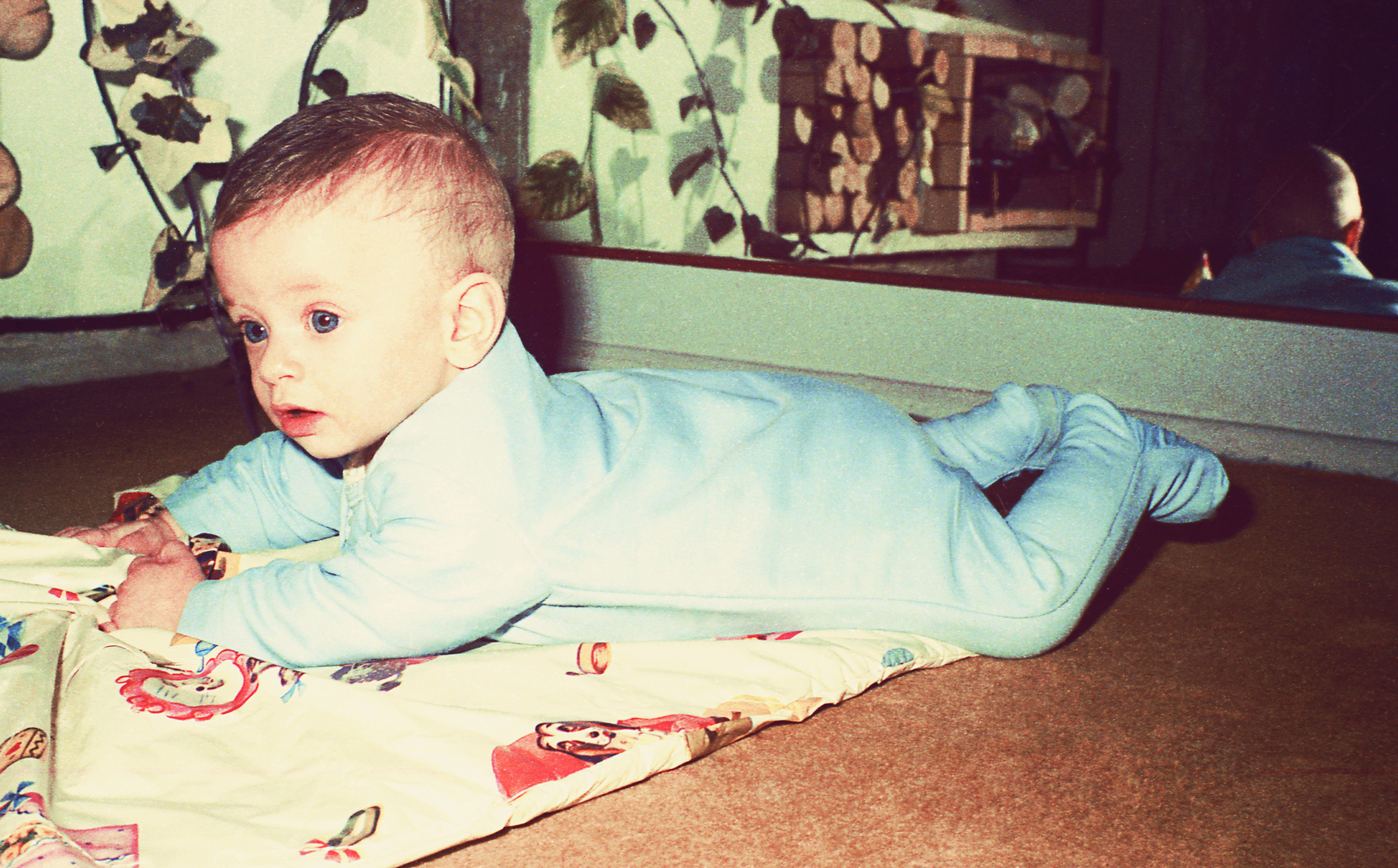 vintage color image of a cute baby boy laying on floor.
