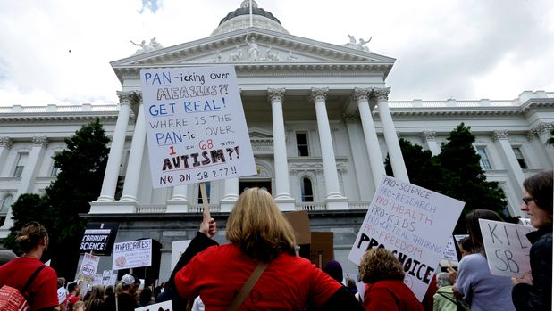 Kelly Trutter, back to camera, joined others protesting against a measure requiring California schoolchildren to get vaccinated,   at a Capitol rally in Sacramento, Calif., Wednesday, April 8, 2015. The bill SB277 by Sen. Richard Pan, D-Sacramento, and Sen. Ben Allen, D-Santa Monica, will be heard by the California Senate Health committee Wednesday. If approved by the Legislature and signed by the governor, parents could no longer cite personal beliefs or religious reasons to send unvaccinated children to private and public schools unless a child's health is in danger. (AP Photo/Rich Pedroncelli)