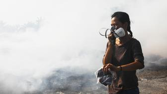 Phua, a volunteer walks past an open burning site inside a palm oil estate in Kuala Langat, Selangor, Malaysia, Saturday, Feb. 2, 2019. (Joshua Paul for Huff Post)