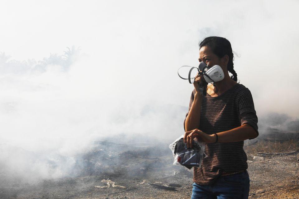 Pua, a volunteer, walks past an open burn site at a palm oil estate in Kuala Langat, Selangor, Malaysia, on Feb. 2, 2019.