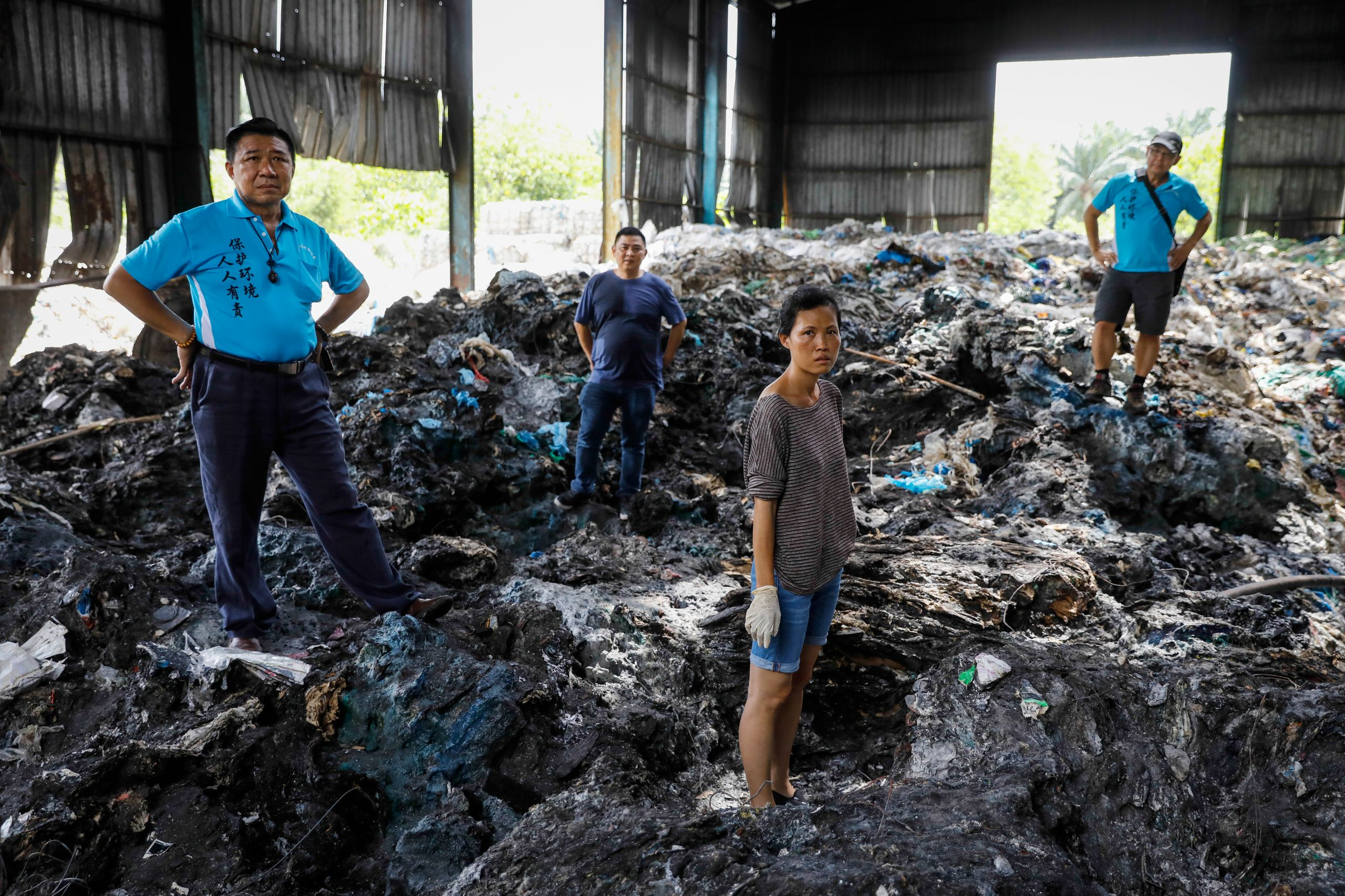 Pua poses with volunteers at an illegal plastic recycling factory in Kuala Langat on Feb. 2, 2019.