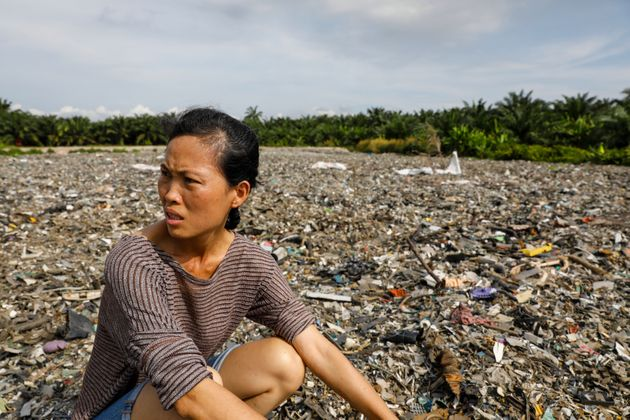A Malaysian activist checks out an illegal plastic dumping site inside a palm oil estate in Kuala Langat....