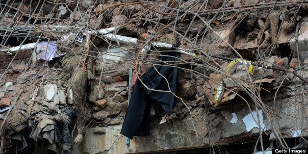 The bodies of Bangladeshi garment workers lie crushed under rubble after an eight-storey building collapse in Savar, on the o