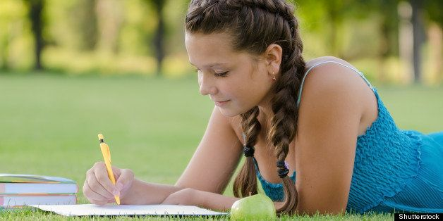Young beautiful girl writing into her notebook in the park