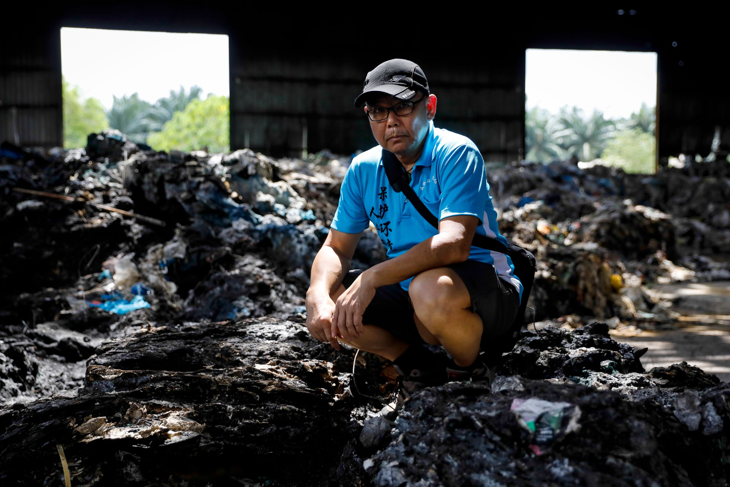 C.K., a volunteer, poses for a portrait at an illegal plastic recycling factory in Kuala Langat.