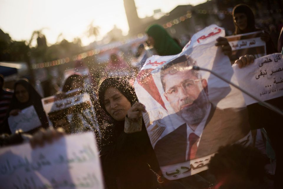 A supporter of Egypt's ousted President Mohammed Morsi sprays water on an Egyptian woman during a protest near Cairo Universi