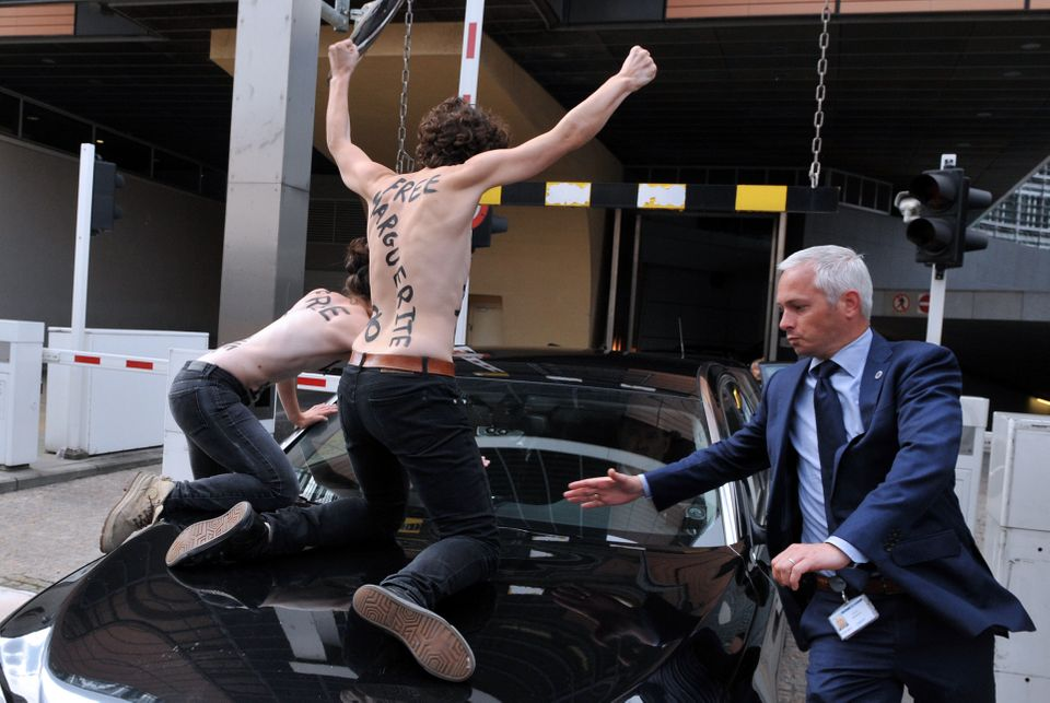 Femen activists try to stop the car of Tunisian Prime Minister from leaving the EU commission building after his working sess