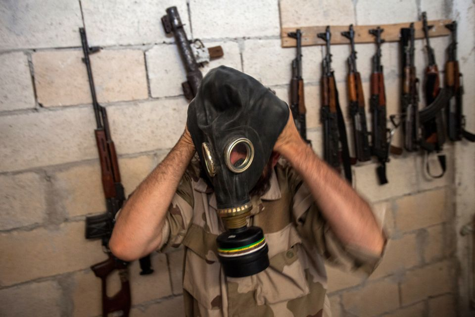 A Syrian rebel tries on a gas mask seized from a Syrian army factory in the northwestern province of Idlib on July 18, 2013.