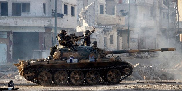 Syrian army troops drive through the ravaged streets of Qusayr in the central Homs province on June 5, 2013, after government