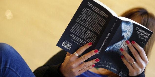 A picture taken on October 16, 2012 shows a woman reading a copy of 'Fifty Shades of Grey' ('Cinquante nuances de Grey' in Fr