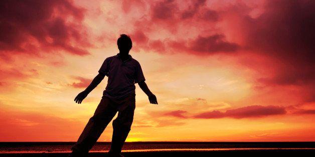 Senior man performing Chinese Tai Chi Kung Fu under sunset at beach.