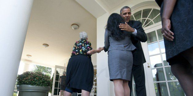 US President Barack Obama hugs a woman who will benefit from health insurance plans under the Affordable Care Act after speak