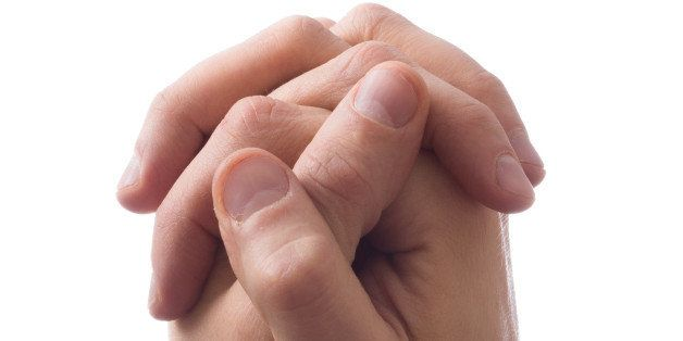 hands clasped together for a...