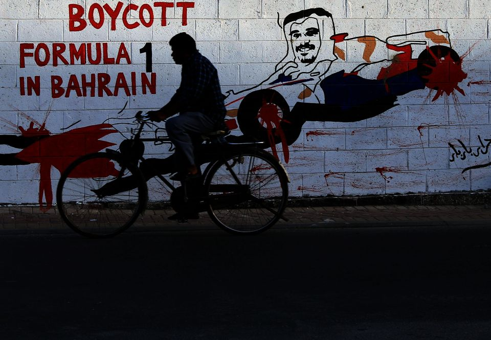 An Asian man rides his bicycle past graffiti on a wall urging a boycott of the April 21 Formula One Bahrain Grand Prix with a