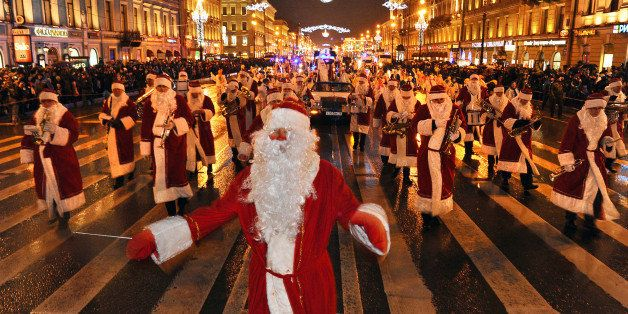 Musicians wearing Santa Claus costumes march along Nevsky Prospect during a New Year's eve festival parade in central St. Pet