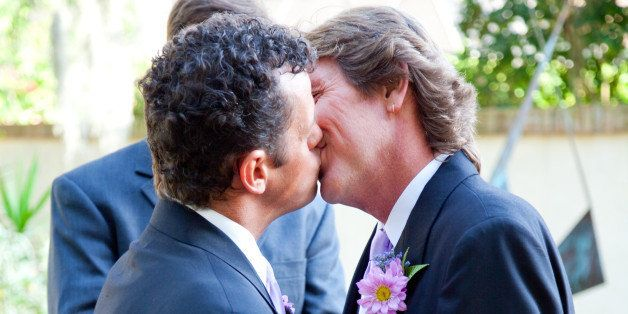 handsome gay couple kissing at...