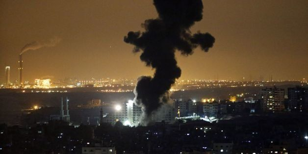 Smoke billows from buildings following an Israeli air strike in Gaza City on July 12, 2014. At least 15 Palestinians were kil