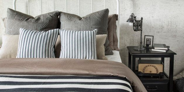 Striped and patterned pillows and blanket on bed