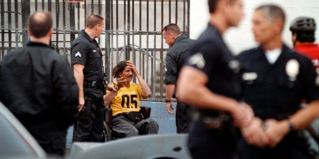 383367 20: Los Angeles Police officers show up in abundance as backup during the arrest of a man in a wheelchair in a very hi