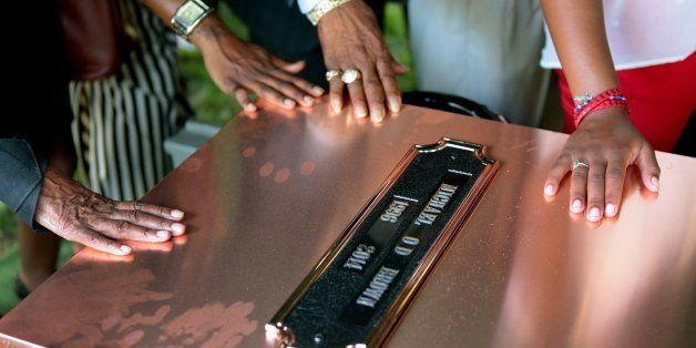 FILE - In this Monday, Aug. 25, 2014, file photo, family members touch the copper top of the vault containing the casket of M
