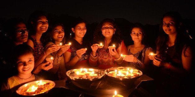 BHOPAL, INDIA - OCTOBER 22: Girls light earthen lamps on the eve of Hindu festival Diwali on October 22, 2014 in Bhopal, Indi