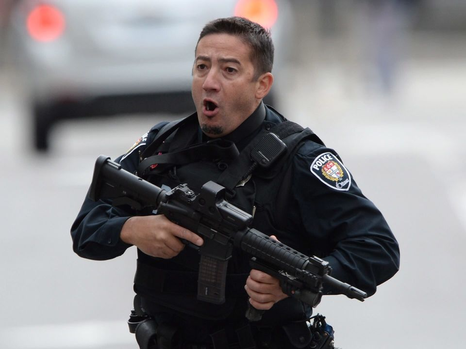 An Ottawa police officer runs with his weapon drawn, outside Parliament Hill in Ottawa, on Oct. 22, 2014.