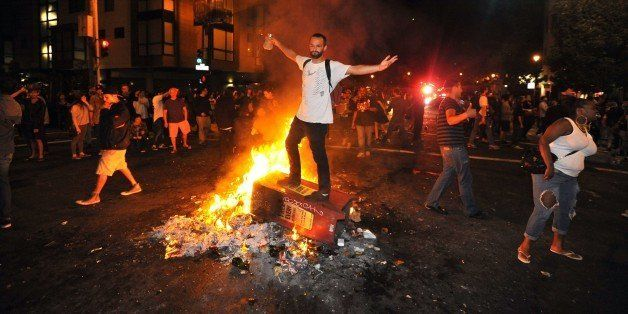 A man stands atop a burning newspaper stand in San Francisco's Mission district in California after the San Francisco Giants